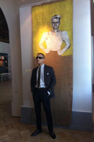 "Georgy Gurianov standing in front of Evgenij Kozlov's painting ""Portrait of Georgy Gurianov"". Exhibition view, 2013."